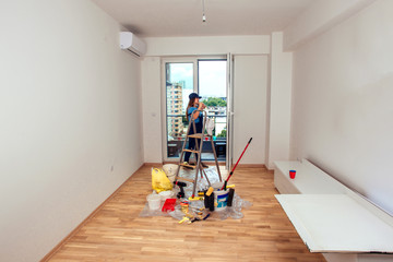 Cute Girl Prepare For Painting Wall In The Room. Young couple home renovation concept.
