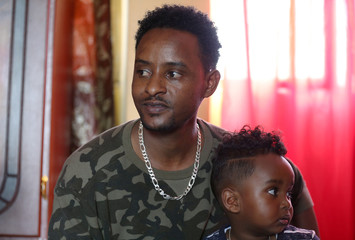 Henok Asgedom, an Eritrean refugee sits in his apartment with his son, Nebiyu Henok, 2, in Addis Ababa