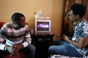Mikael Andemariam and Nahom Eyob former Eritrean military officers and refugees watch the Eritrean TV in their apartment in Addis Ababa