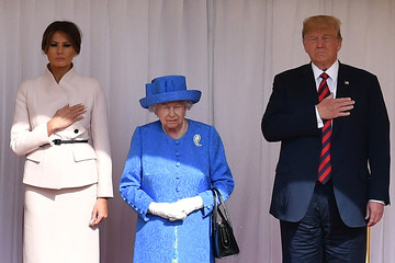 U.S. President Donald Trump and First Lady Melania Trump stand with Britain's Queen Elizabeth on the dais during the U.S. national anthem in the Quadrangle at Windsor Castle, Windsor