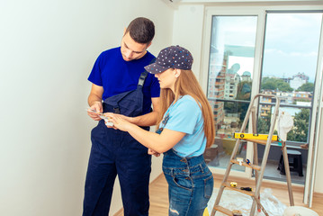 Sweet Couple Choosing Color From Color Guide. Young couple home renovation concept.