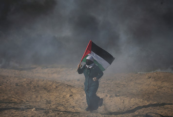 Demonstrator holds a Palestinian flag during a protest at the Israel-Gaza border in the southern Gaza Strip