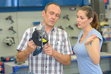 Man and woman looking at circular saw