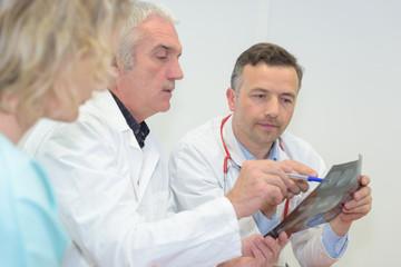 three doctors looking at x-ray
