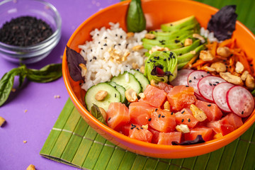 Hawaiian salad Poke with salmon fish, avocado, Korean carrots, cucumbers, radish and rice, with black sesame. in an orange plate. On the purple trend background of 2018. copy space, top view