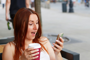 Suprised young beautiful redhead woman looking on her smartphone and reading sms