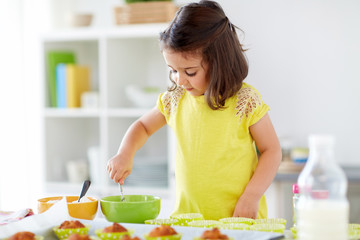 family, cooking, baking and people concept - little girl making batter for muffins or cupcakes at home kitchen