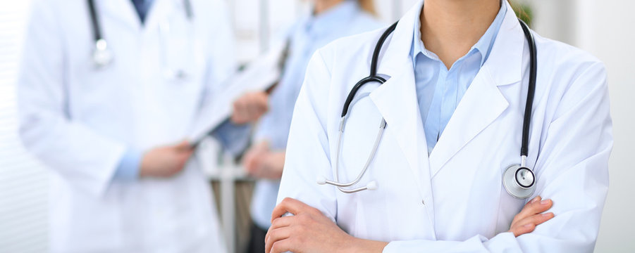 Female doctor standing straight in hospital. Closeup of stethoscope at practitioner breast. Medicine and health care concept