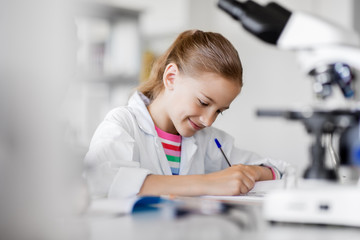 education, science and children concept - girl studying chemistry at school laboratory and writing...