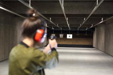 Na strzelnicy. Kobieta celuje do papierowej tarczy