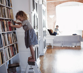 Side view of girl standing by bookshelves on ladder with brother in background at home