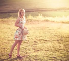 Girl in golden sunset light, summer meadow background