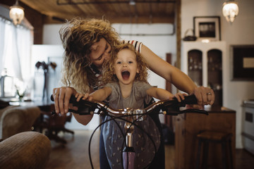 Cheerful mother with daughter riding bicycle at home
