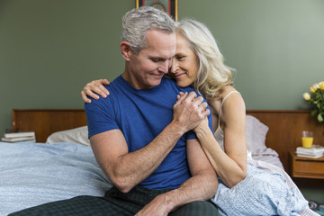 Loving man holding woman's hand while sitting on bed at home