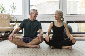 Smiling couple looking each other face to face while exercising at home