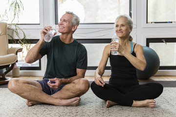 Smiling couple drinking water from bottles while exercising at home