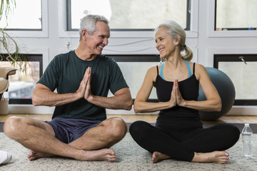Full length of smiling couple with hands clasped looking each other face to face while meditating at home