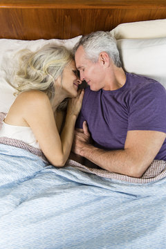 Overhead view of senior couple sleeping together on bed at home