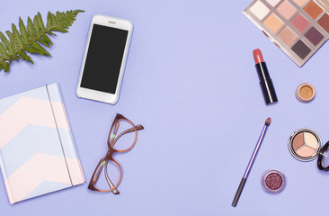 beautiful girl accessories, top view of women's things: a notebook, phone, glasses, cosmetics, eye shadows, lipstick, make-up brush, blush, eyeliner. violet background with place for text. flat lay