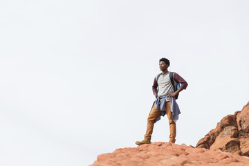 Low angle view of man with hands on hip looking away while standing on rock formation against clear sky