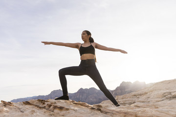 Woman practicing warrior pose on rock formation against sky