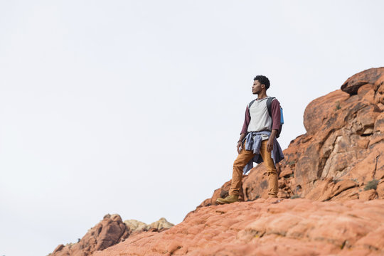 Low angle view of man looking away while standing on rock formation against clear sky