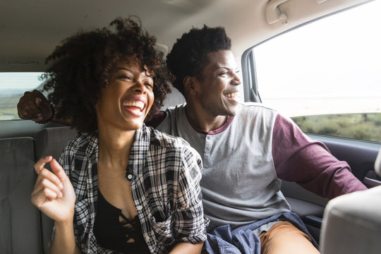 Happy couple traveling in car