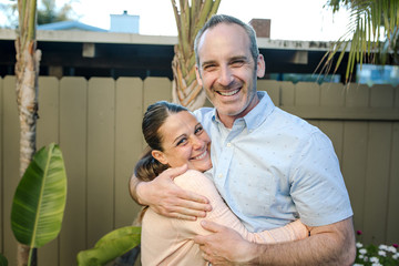 Portrait of happy husband embracing wife while standing against fence at yard