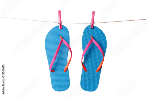 5b8b33d56a7 Blue flip flops hanging on clothesline isolated on a white background.  Vacation concept