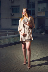 Fashionable brown-haired woman with make-up and in stylish clothes with a short skirt posing on the evening street of the city.