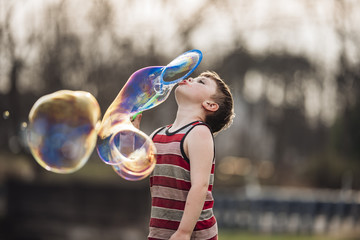 Boy blowing bubbles while playing at park