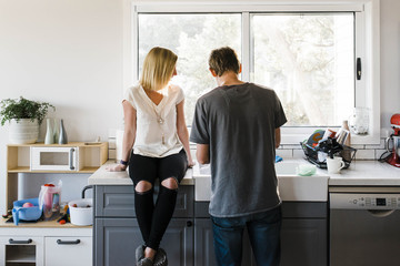 Woman sitting on kitchen counter by man at home