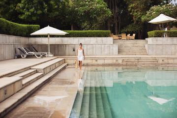Woman in white dress near swimming pool