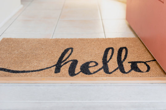 Open door with a natural fiber rug with the word hello written in script