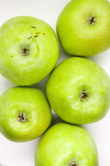 Green apple is lying  on a white background