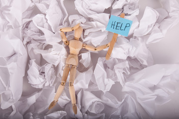 Manikin doll frustrated holding a help sign laying on crumbled sheets of paper