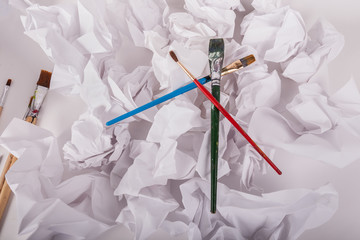 Three artist paintbrushes laying on crumbled up balls of white copier paper