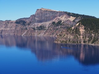 The magnificent rich blue waters of Crater Lake with reflections of the rim in the forests of Southern Oregon on a beautiful sunny summer morning.