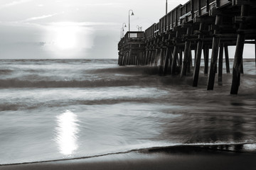 A black and white photograph of the Sandbridge Fishing Pier in Sandbridge Virginia, Virginia Beach during a sunrise.  A long shutter speed makes the water silky and dreamy.