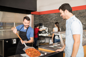 Canvas Prints Pizzeria Smiling chef putting pizza on plate using shovel while customer is watching