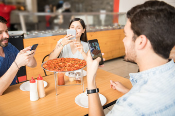 Happy friends using smartphone to take pizza photo