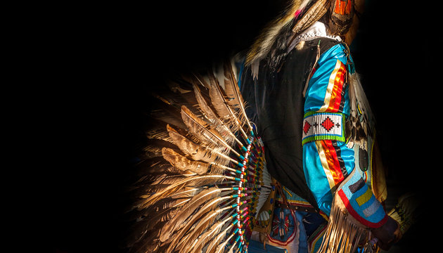 Native American Indian. Close up of colorful dressed native man isolated on black background.