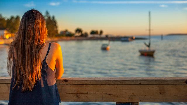 Young lady watching boats sailing away at dusk.