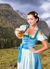 junge Frau im Dirndl mit Bier vor Alpenlangschaft
