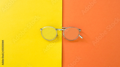 Wall mural Topview Glasses on yellow and orange background.Color creative concept