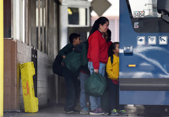 Undocumented immigrants board a bus at a bus station in San Antonio