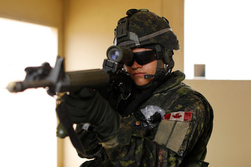 A Canadian soldier with the Royal 22e Regiment takes aim from his position as they conduct assault operations during a Rim of the Pacific (RIMPAC) exercise with U.S. Marines at Camp Pendleton