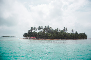 Tropical paradise island with small hut in the middle of the turquoise blue Caribbean Sea in the San Blas Islands, off the coast of Panama
