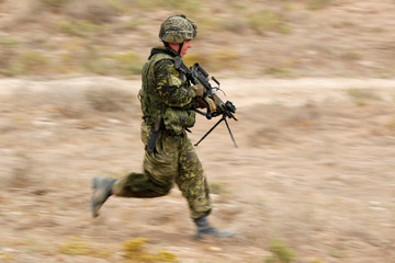 A Canadian soldier with the Royal 22e Regiment runs to a position as they conduct assault operations during a Rim of the Pacific (RIMPAC) exercise with U.S. Marines at Camp Pendleton