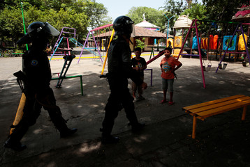 Riot police officers walk past children during clashes with anti-government protesters in the indigenous community of Monimbo in Masaya, Nicaragua